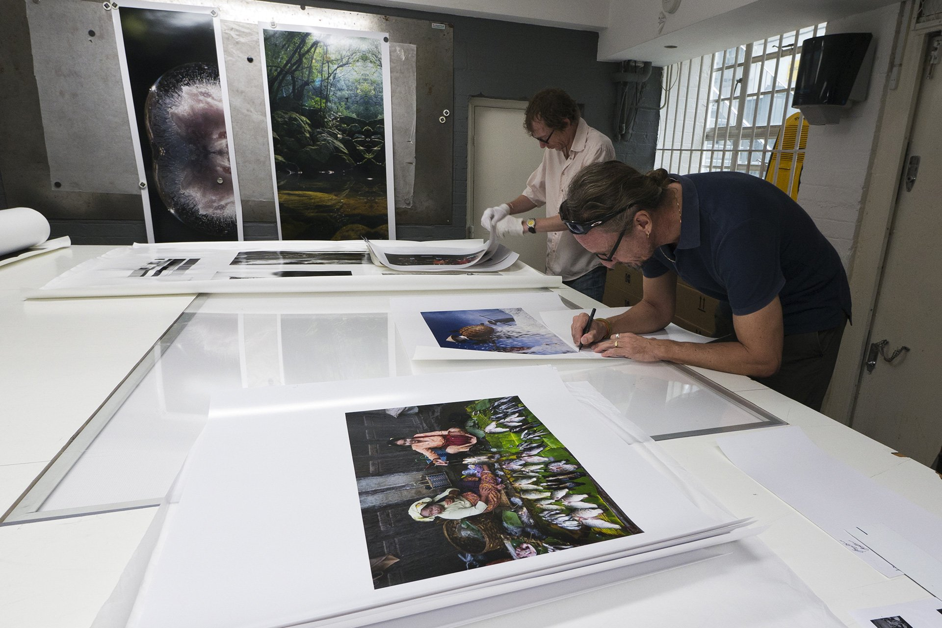 Hans signing fine art prints for his London exhibition. OXO Tower Wharf, London, UK.