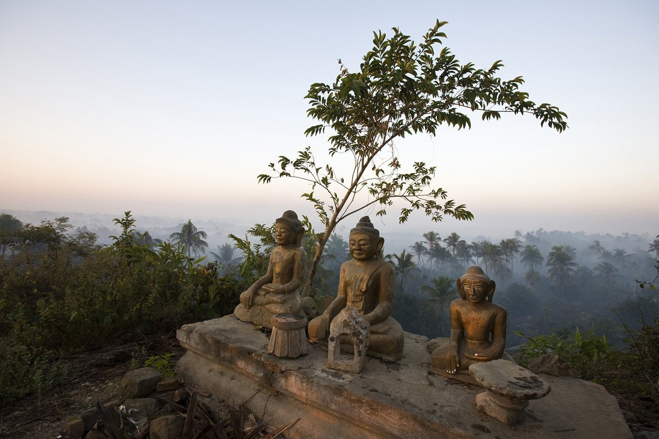Three Buddha statues sitting on one of the hill tops surrounding the stupa studded valley of Mrauk U.