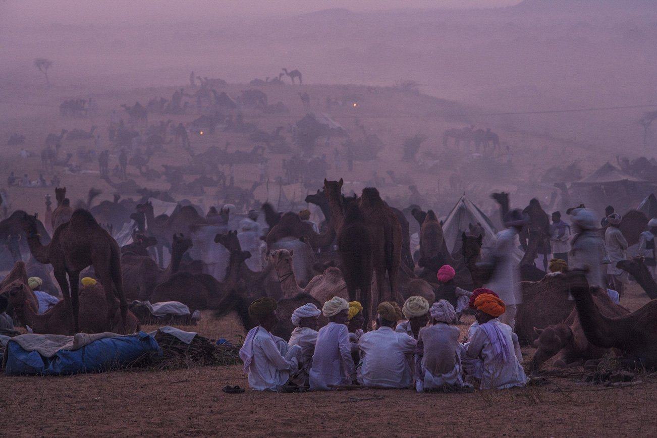 The camel fair at dusk, when traders discuss the affairs of the day while sitting around small fires.