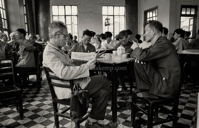 Men relaxing in a traditional teahouse in the southern Chinese city of Guangzhou, ca 1990. Note the birdcage hanging in the window, the bird singing for the enjoyment of patrons. In the late 1980's and early 1990's I traveled a lot in China. The country had opened up but the huge wave of modernization had yet to arrive and scenes such as this were still common.