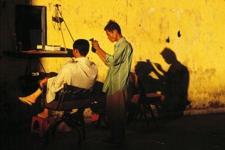 Barber on a streetcorner in Saigon, Vietnam, 1995 - Photography by Hans Kemp