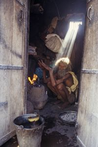 A wandering sadhu (holy man) warms himself over a small fire, India, 1995